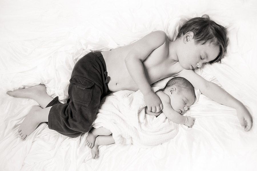 Big brother sleeping with newborn